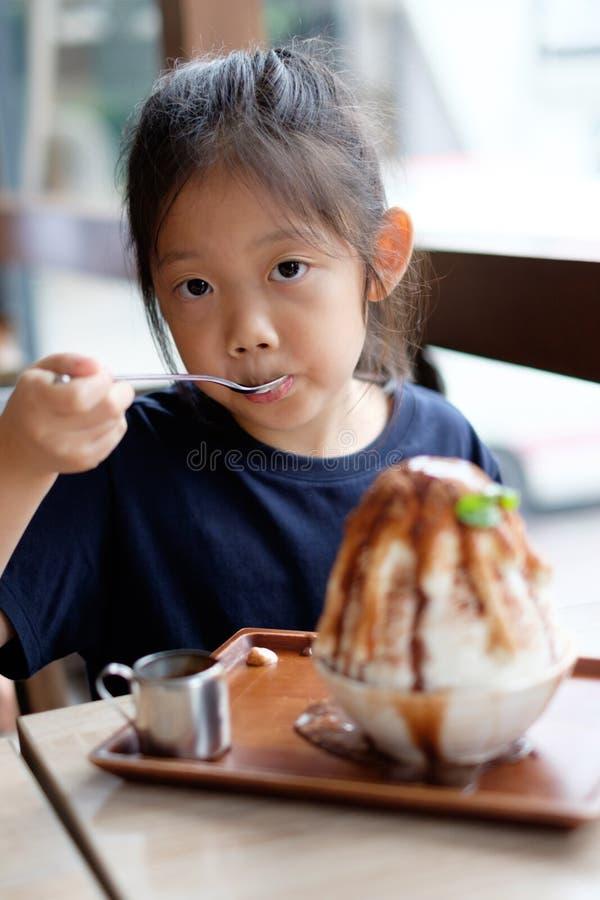 Det asiatiska barnet tycker om att äta den hawaiansk fryste efterrätten för rakningen is royaltyfri bild