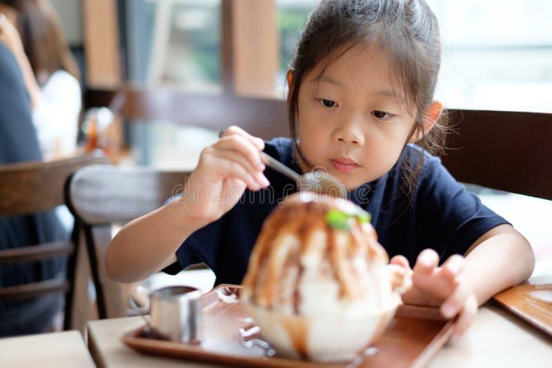 Det asiatiska barnet tycker om att äta korean Patbingsu eller Bingsu, rakningis royaltyfri foto
