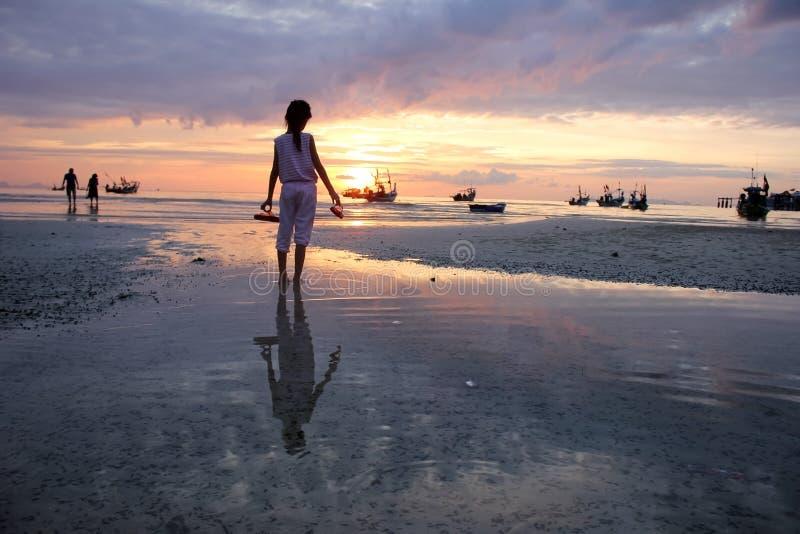 Det asiatiska flickainnehavet skor att se solnedgång på stranden royaltyfri bild