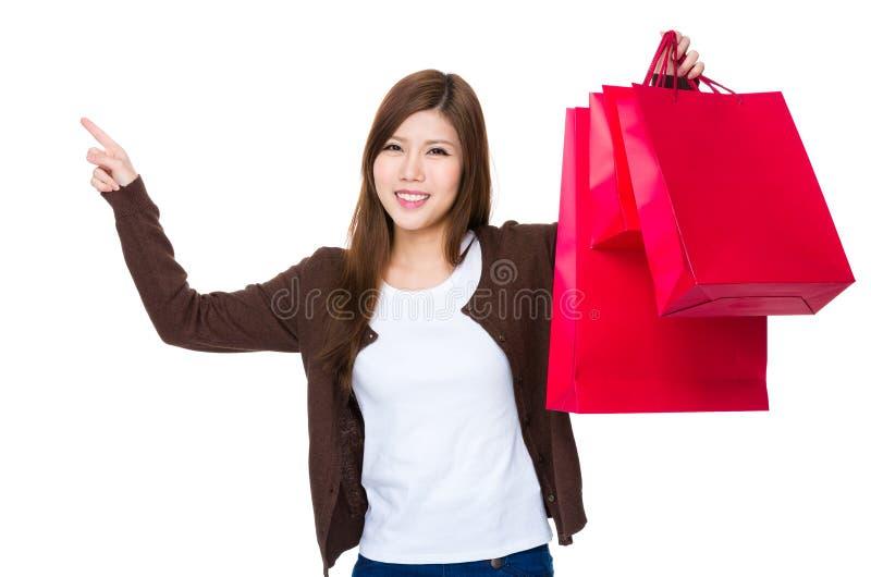 Det asiatiska kvinnainnehavet med shoppingpåsen och fingret pekar upp royaltyfri foto