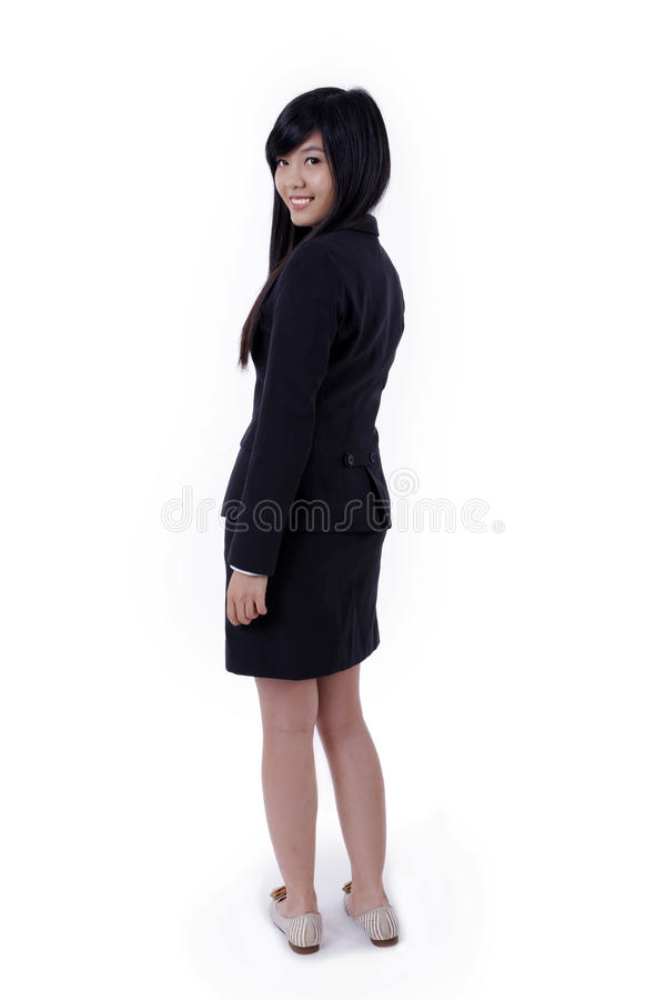 Det asiatiska leendet för affärskvinnan, vänder tillbaka framsidan till kameran arkivbild
