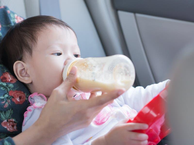 Det asiatiska lilla barnet som äter flaskan av, mjölkar och sitter i bil arkivbilder