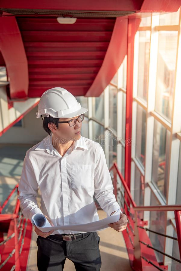 Det asiatiska manliga teknikerinnehavet gör en skiss av på konstruktionsplatsen royaltyfri bild