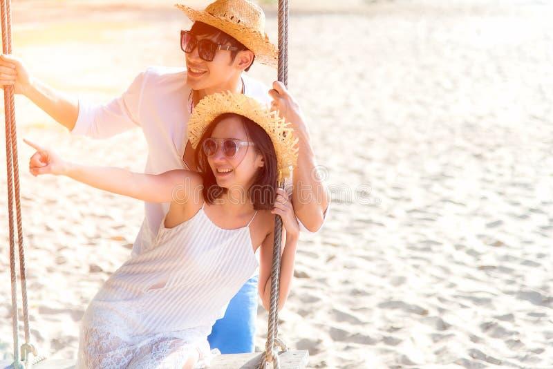 Det asiatiska romantiska paret sitter på havsstranden på repgunga kopplar av och lycka för ferie arkivfoton
