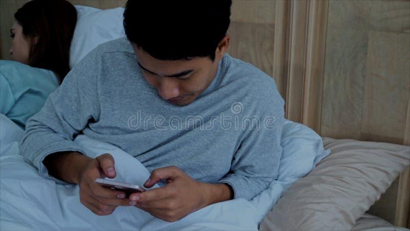 Det asiatiska unga gifta paret använde smartphonen som pratar på säng royaltyfri foto