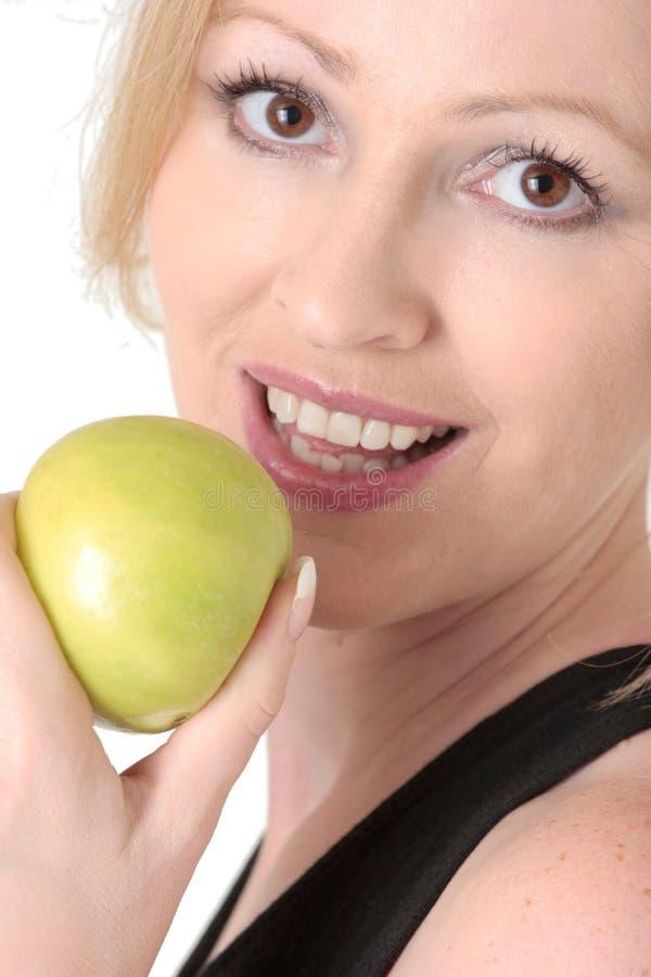 det attraktiva äpplet äter till kvinnan royaltyfri fotografi