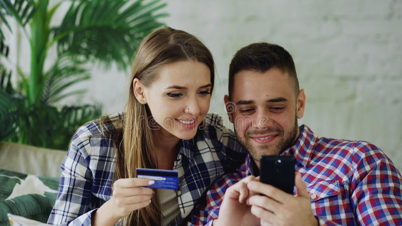 Det attraktiva barnet kopplar ihop med smartphonen, och kreditkortshopping på internet sitter på soffan i vardagsrum hemma arkivfoton
