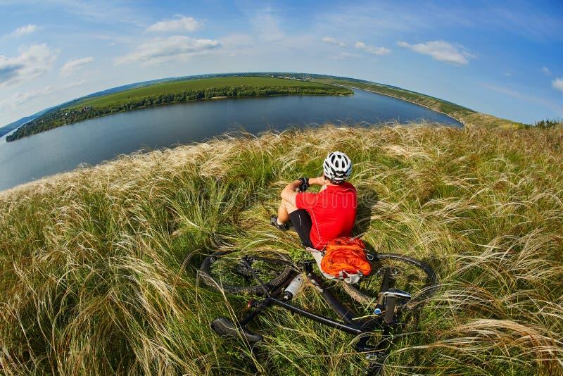 Det attraktiva cyklistsammanträdet på gräset på ängen med mountainbiket ovanför floden royaltyfria bilder