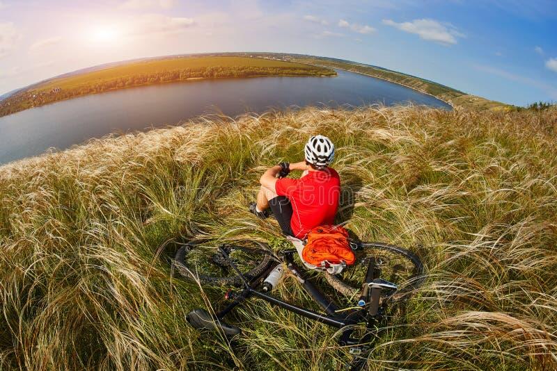 Det attraktiva cyklistsammanträdet på gräset på ängen med mountainbiket ovanför floden royaltyfri bild