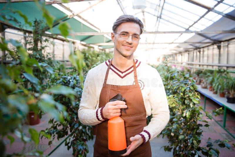 Det attraktiva manliga trädgårdsmästareanseendet och innehavet bevattnar pulveriser royaltyfri bild