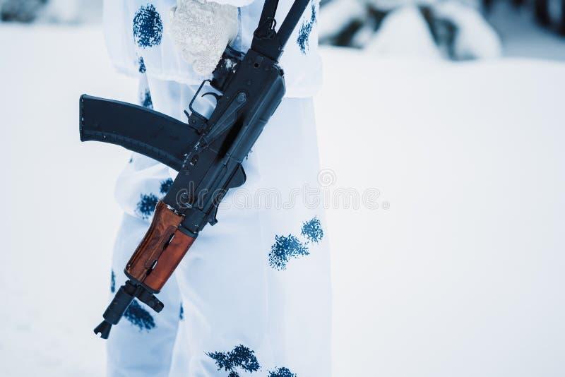 Det automatiska geväret rymmer en terrorist i vit kamouflage royaltyfri bild
