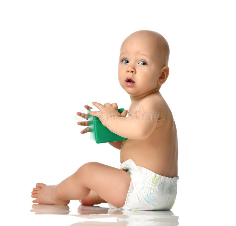 Det begynnande barnet behandla som ett barn att sitta för pojkelitet barn som är naket i blöja med den gröna tegelstenleksaken so royaltyfria bilder