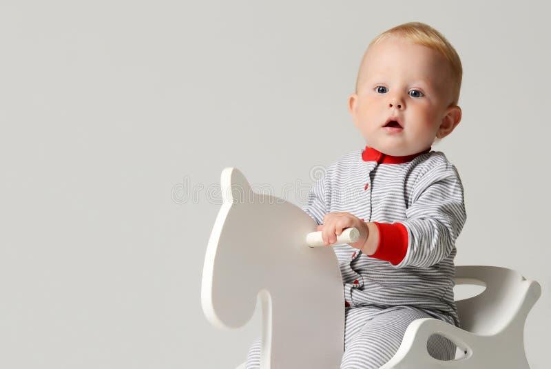 Det begynnande barnet behandla som ett barn leksaken för hästen för ritten för sammanträde för pojkeungelilla barnet den vita lil royaltyfri foto