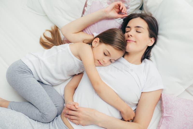 Det behog lilla barnet sover nära hennes moder, omfamnar med förälskelse, har angenäma drömmar, lögn på bekväm säng Mum och gulli arkivbild