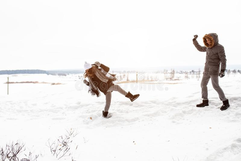 Det bekymmerslösa lyckliga barnet kopplar ihop att ha gyckel i insnöat kasta för vinterskogsmark kastar snöboll tillsammans på de royaltyfri bild
