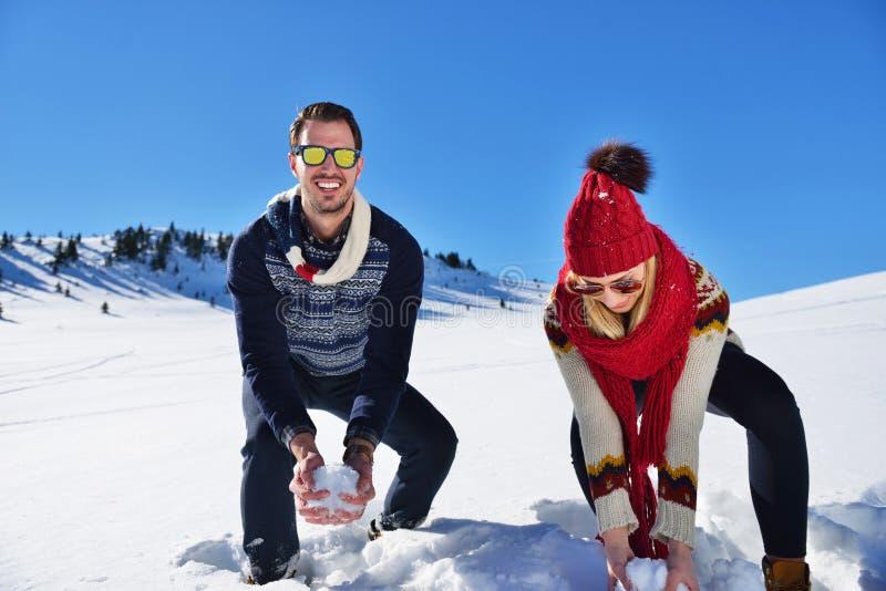 Det bekymmerslösa lyckliga barnet kopplar ihop att ha gyckel tillsammans i snö fotografering för bildbyråer