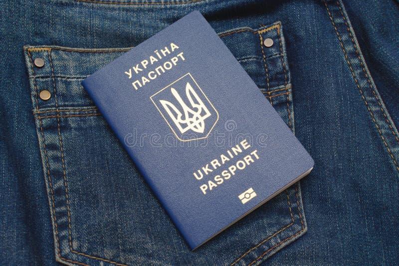 Det Biometric passet av Ukraina på jeans stoppa i fickan royaltyfri fotografi