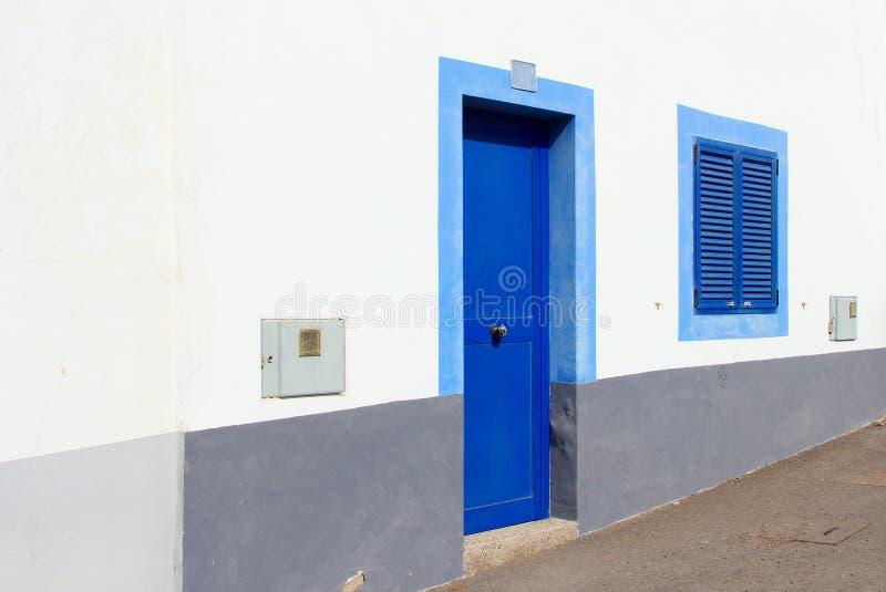 Det blåa dörrfönstret stänger med fönsterluckor det vita huset, kanariefågelöar, Spanien fotografering för bildbyråer
