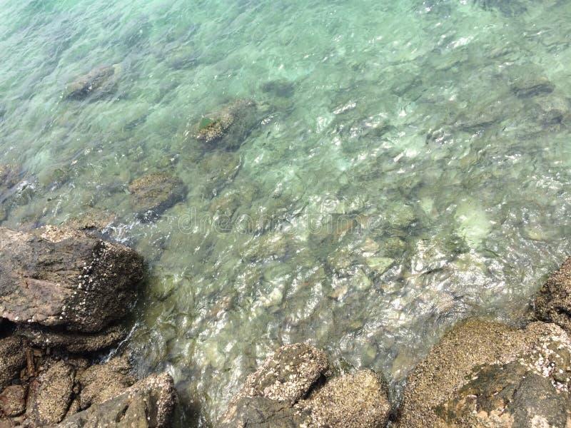 Det blåa havet på vaggar längs kusten royaltyfri foto