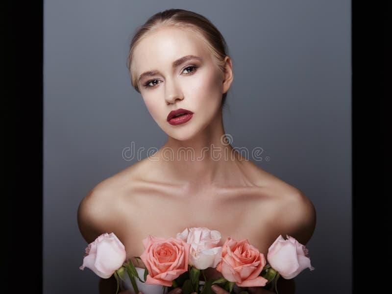 Det blonda flickainnehavet steg blommor nära hennes framsida Skönhetstående av en kvinna på en mörk bakgrund Perfekt makeup, härl royaltyfri foto