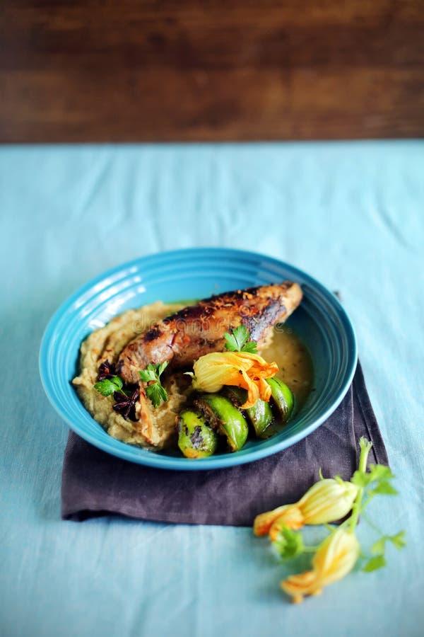 Det bräserade rabitbenet med grönsaken mosar, figues, och zucchinin blommar royaltyfri fotografi
