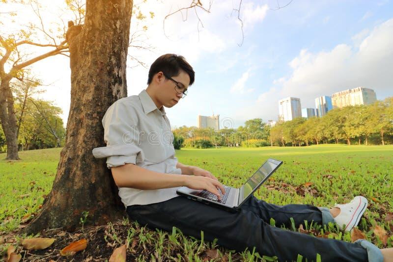 Det breda vinkelskottet av lycklig maskinskrivning för den unga mannen på en bärbar datordator för hans arbete i en härlig stad p arkivfoton