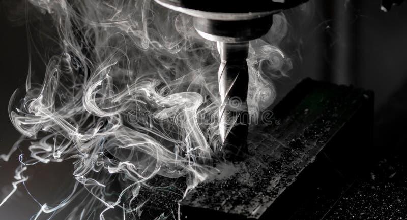 Det Bridgeport CNC-slutet maler fullföljande av en bunt av stålplattan med metallarkiveringschiper och tung rök royaltyfri fotografi