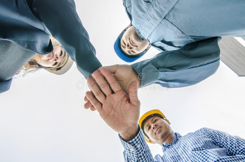 det byggnads-, partnerskap-, gest- och folkbegreppet och att stapla händer uttrycker deras teamwork och samarbete royaltyfri foto