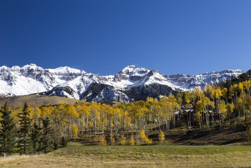 Det Colorado landskapet med det stora huset som kura ihop sig bland färgrika träd, och snö nådde en höjdpunkt berg royaltyfria bilder