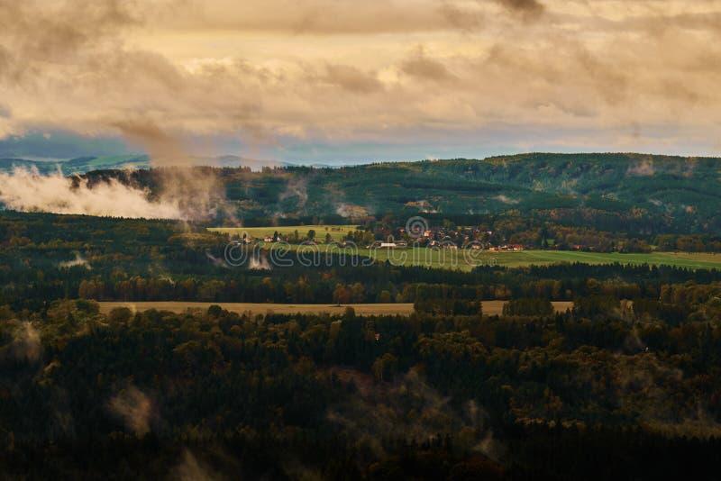 Det dimmiga regniga morgonlandskapet med de steniga montainsna f?r sand i den bohemiska anglosaxaren Schweiz i h?st f?rgar arkivfoton