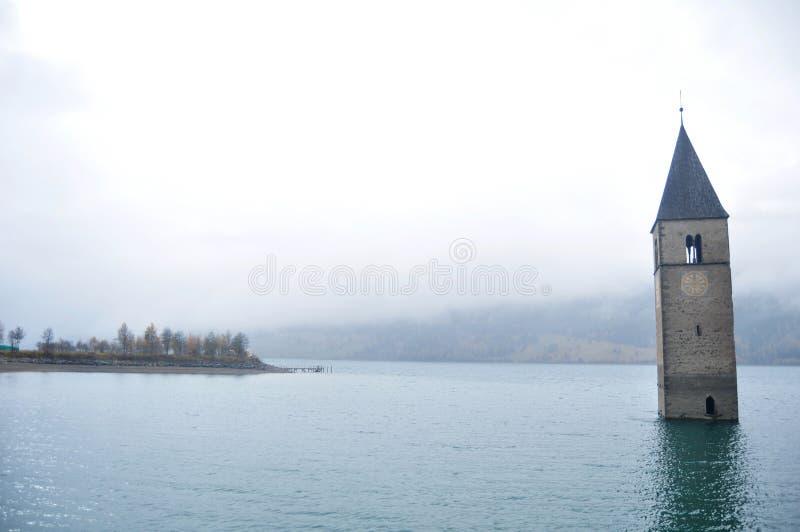 Det doppade tornet av reschenseekyrkan djupt i Resias sjön av Bolzano eller bozen på Italien fotografering för bildbyråer