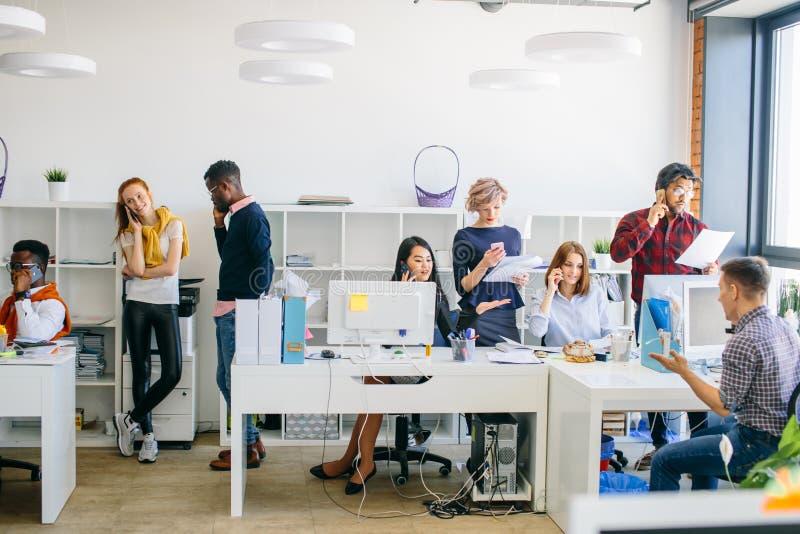 Det driftiga kontorsfolket använder mobiltelefoner på arbete royaltyfri bild