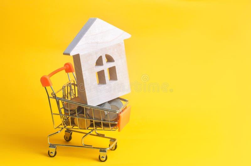 Det egenskapsinvesteringen och huset intecknar finansiellt begrepp köpa, hyra och sälja lägenheter Mynt och ett trähus i ett sh fotografering för bildbyråer
