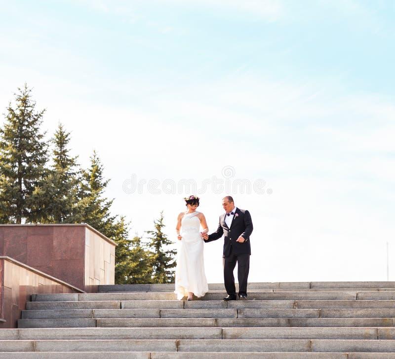 Det eleganta stilfulla barnet kopplar ihop den härliga bruden och brudgummen på trappan royaltyfria bilder