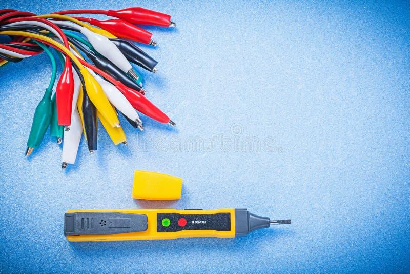 Det elektriska gemet för testerindikatorkrokodilen kablar på blå backgrou royaltyfri bild