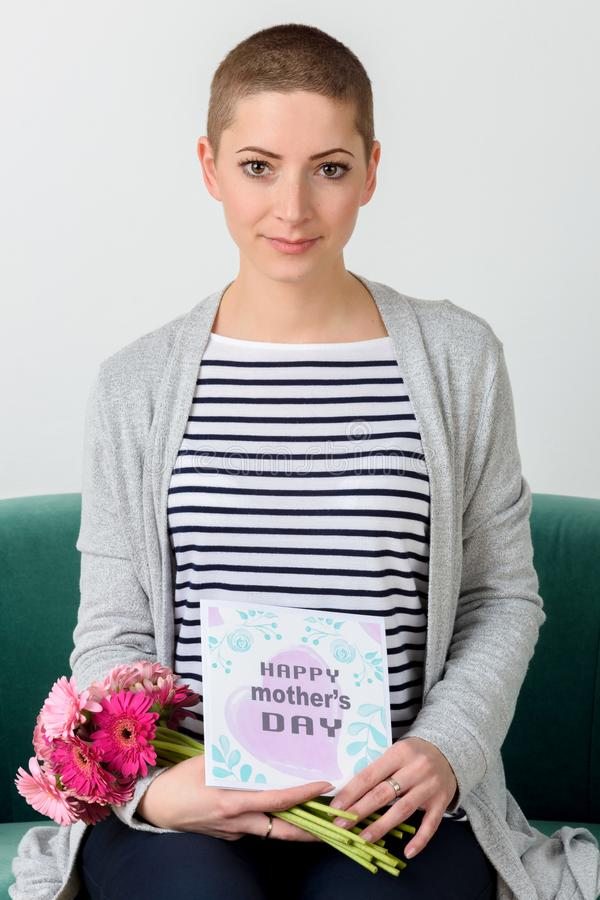 Det emotionella barnet fostrar den hållande buketten av gerberatusenskönor och läsning hennes kort för dagen för moder` s arkivbilder