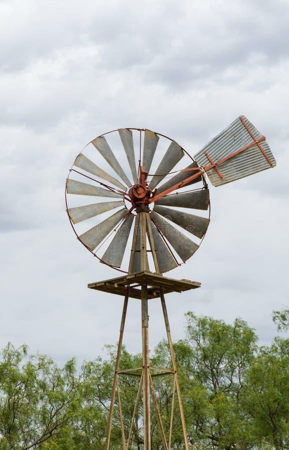 Det enkla gamla historiska vindhjulet eller vindpumpen som göras av trä och metall stänger sig upp royaltyfri fotografi
