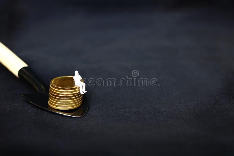 Det enkla vita miniatyraffärsfolket som sitter på guld- mynt, traver på den svarta skyffeln, på svart bakgrund, att gräva för beg arkivbild
