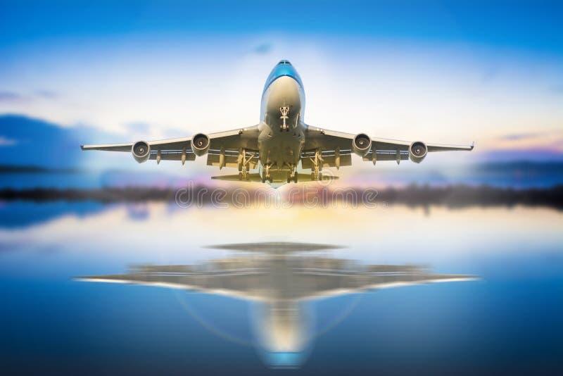 Det enorma passagerareflygplanet flyger under en härlig solnedgång arkivbild