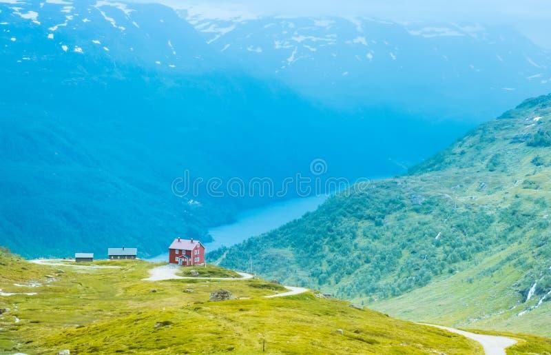 Det ensamma huset på bergsjön i Norge royaltyfri fotografi