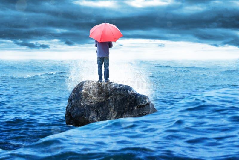 Det ensamma mananseendet vaggar på med det röda paraplyet arkivbild