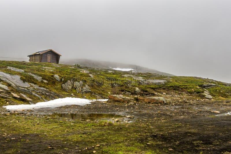 Det ensamma trähuset står på kullen bland den norr Norge naturen arkivbild