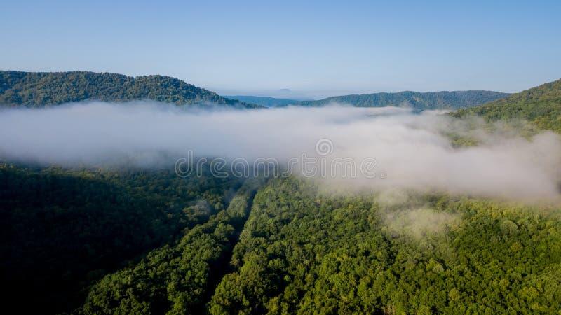 Det episka flyg- flyget till och med berget fördunklar på härlig morgon för soluppgång royaltyfria bilder