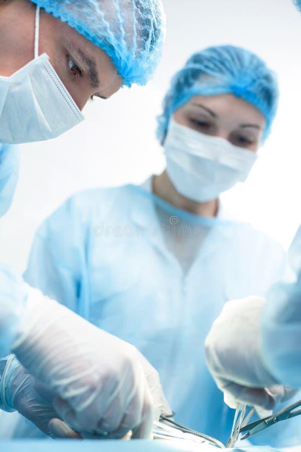Det erfarna kirurgiska laget gör deras arbete arkivbild