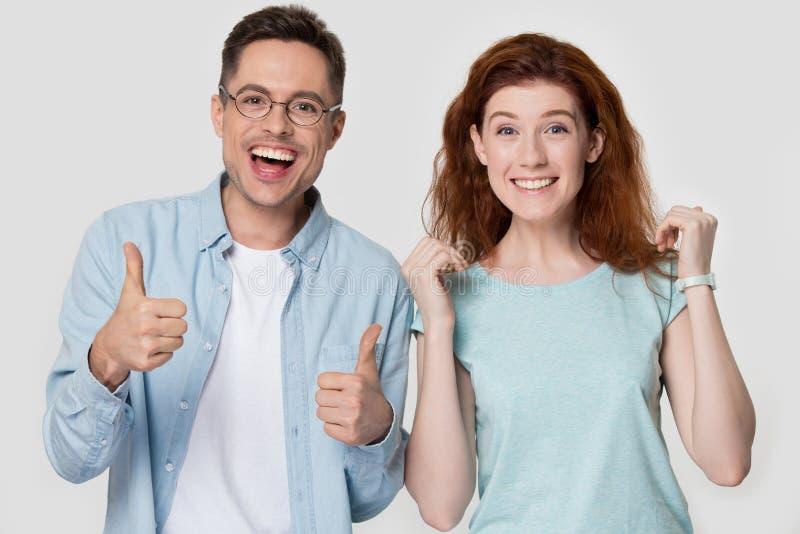 Det extatiska paret känner lyckliga showtummar som isoleras upp på grå färger royaltyfri fotografi