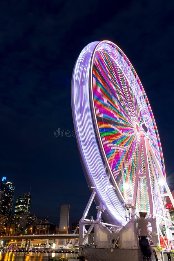 Det färgrika ferrishjulet tänder upp natten royaltyfri foto