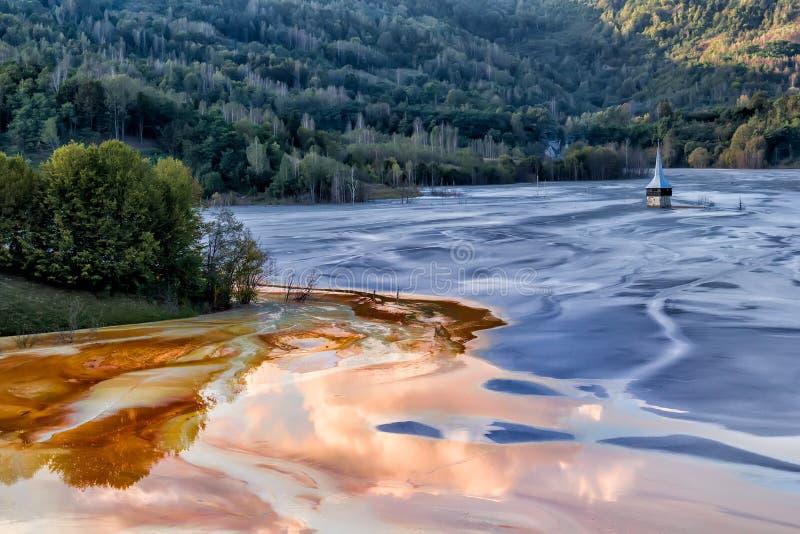 Det färgrika landskapet av en översvämmad kyrka i gift förorenade kopparbryta för sjön tack vare royaltyfri bild