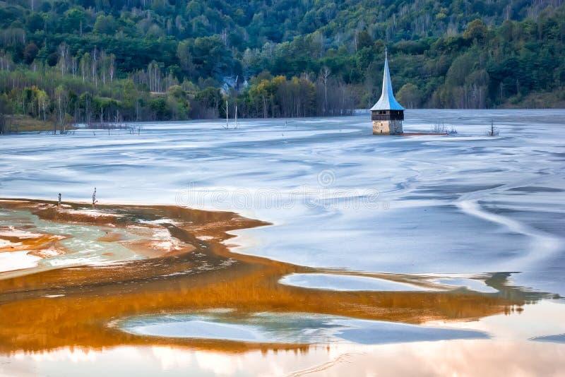 Det färgrika landskapet av en översvämmad kyrka i gift förorenade kopparbryta för sjön tack vare arkivfoton