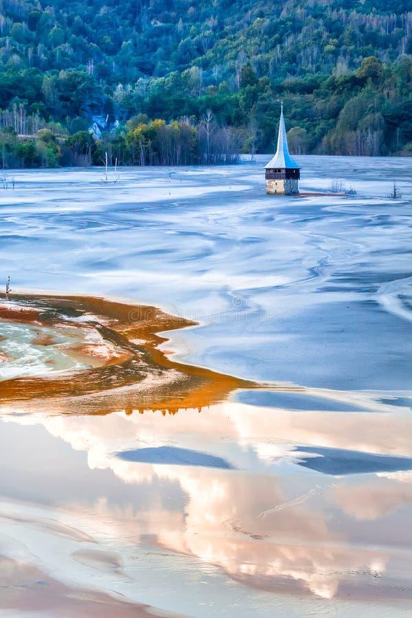 Det färgrika landskapet av en översvämmad kyrka i gift förorenade kopparbryta för sjön tack vare royaltyfri foto