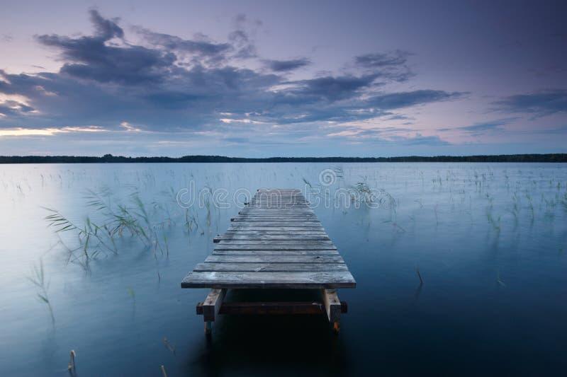 Det färgrika landskapet med himmel och träbryggapir reflekterade i sjön på aftonen arkivbilder